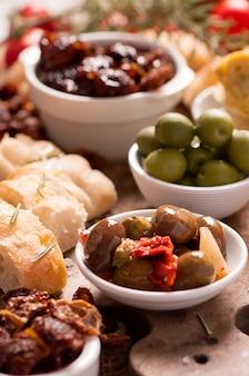 Świeże oliwki i oliwa z oliwek na rustykalnym drewnie