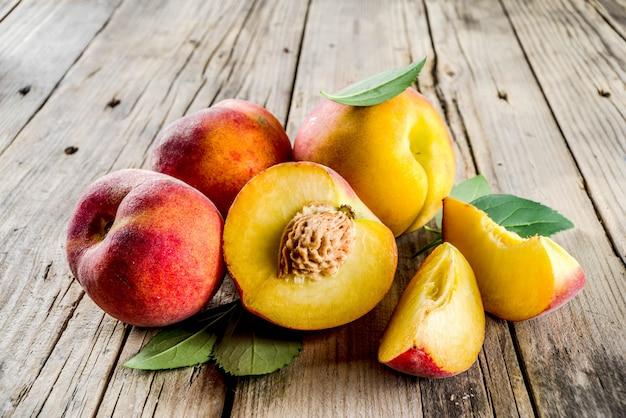 Świeże organiczne brzoskwinie na nieociosanym drewnianym stole