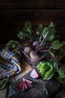 Świeże organiczne buraki czerwone z liśćmi w wiklinowym koszu na drewnianym stole. naturalne organiczne warzywa. jesienne zbiory. rustykalny styl wiejski.