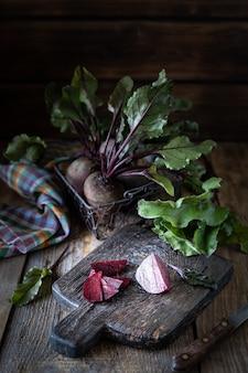Świeże organiczne buraki czerwone z liśćmi w wiklinowym koszu na drewnianym stole. naturalne organiczne warzywa. jesienne zbiory. rustykalny