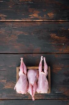 Świeże organiczne całe mięso przepiórcze, widok z góry, na ciemnym tle drewniane z miejsca na kopię