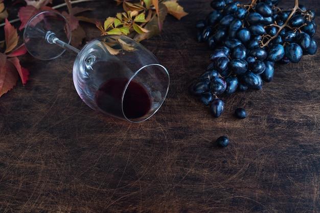 Świeże organiczne czarne winogrona i kieliszek z czerwonym winem na rustykalnym tle sklejki. miejsce na tekst.