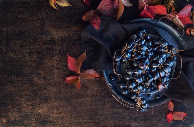 Świeże, organiczne czarne winogrona na tacy vintage na rustykalnej sklejce