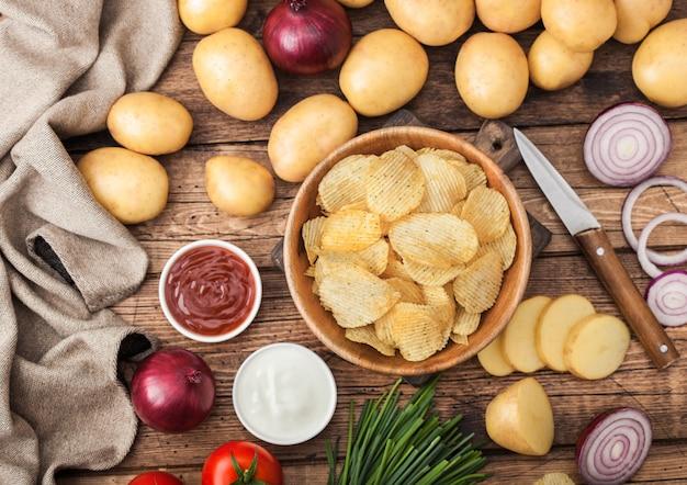 Świeże organiczne domowe chipsy ziemniaczane w drewnianej misce ze śmietaną