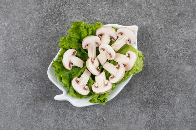 Świeże organiczne grzyby z sałatą na białym talerzu