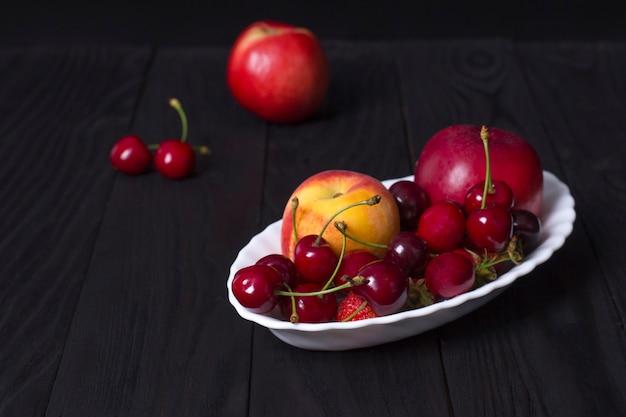Świeże organiczne jagody lato i owoce w białej płytce na czarnym tle.