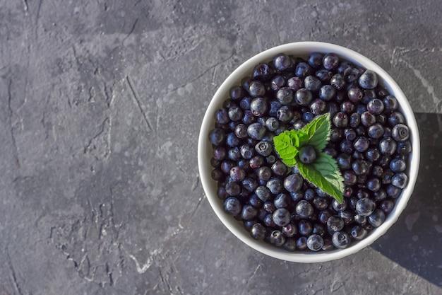 Świeże organiczne jagody w pucharze na zmroku z copyspace.