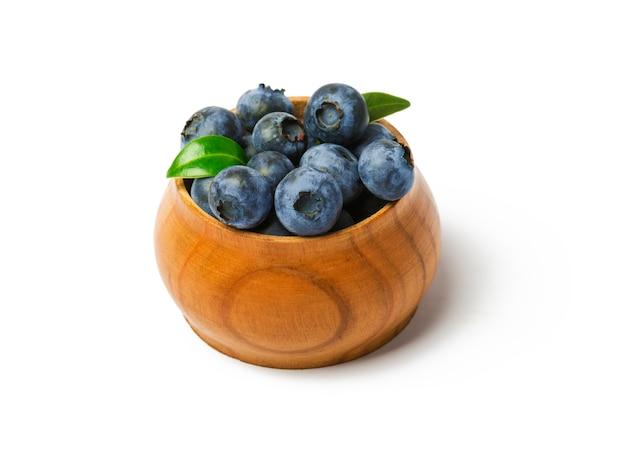 Świeże organiczne jagody z liśćmi w drewnianej misce