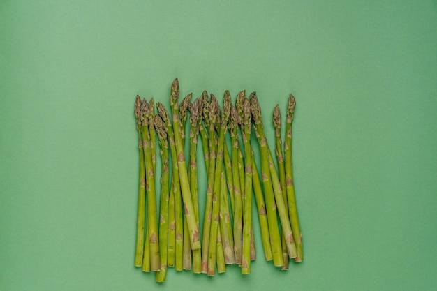 Świeże organiczne kiełki szparagów na zielonym tle z miejsca kopiowania dla swojego projektu. koncepcja zdrowej żywności.