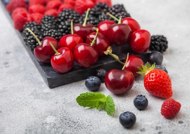 Świeże organiczne letnie jagody mieszają się na czarnej marmurowej desce na tle jasnego stołu kuchennego.