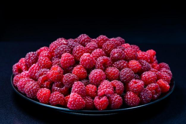 Świeże organiczne maliny czerwone w płytce na czarnej powierzchni