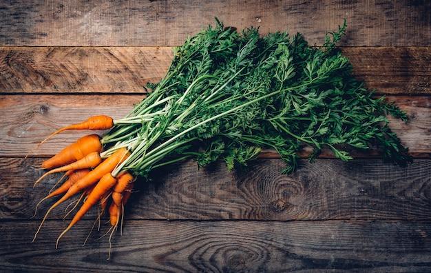 Świeże organiczne marchewki z zielonymi liśćmi na drewnianym.