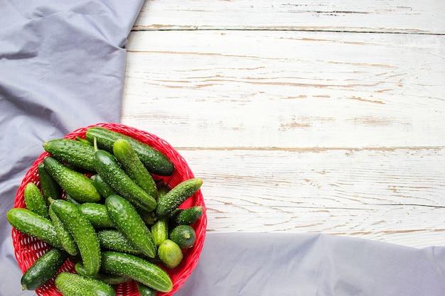 Świeże organiczne ogórki w czerwonym koszu na białym drewnianym stole z zieloną i czerwoną i papryką chili, kopru włoskiego, soli, czarnego pieprzu, czosnku, grochu, z bliska, zdrowe pojęcie, widok z góry, płaskie świeckich