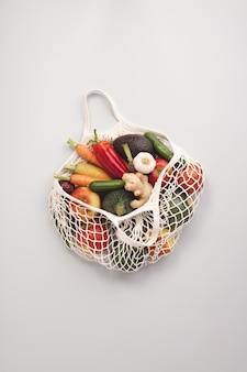 Świeże organiczne owoce i warzywa w siatkowej torbie tekstylnej