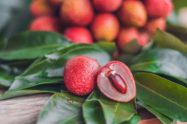 Świeże organiczne owoce liczi i liście liczi na rustykalnym drewnianym