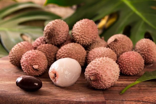 Świeże organiczne owoce liczi na bambusowym koszu i starym drewnianym stole