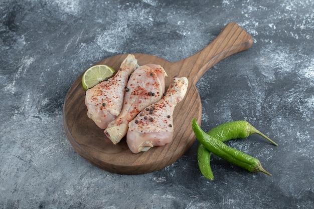 Świeże, organiczne podudzia z kurczaka na drewnianej desce do krojenia.