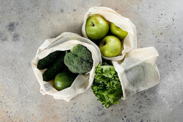 Świeże organiczne warzywa i owoce w ekologicznej torbie wielokrotnego użytku widok z góry na szarym marmurowym tle