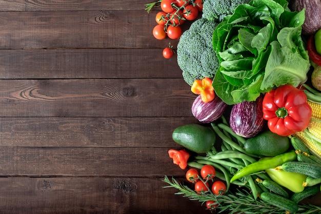 Świeże organiczne warzywa na drewnianym tle z miejsca na kopię. widok z góry
