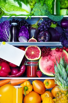 Świeże organiczne zdrowe surowe przeciwutleniacze fioletowe, czerwone, zielone i pomarańczowe jedzenie, warzywa, owoce i soki w wegańskiej wegetariańskiej lodówce: figa, pomarańcze, arbuz, ananas, sałatka, pieprz, zielony, pomelo.