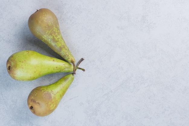Świeże organiczne zielone gruszki na szarym tle.