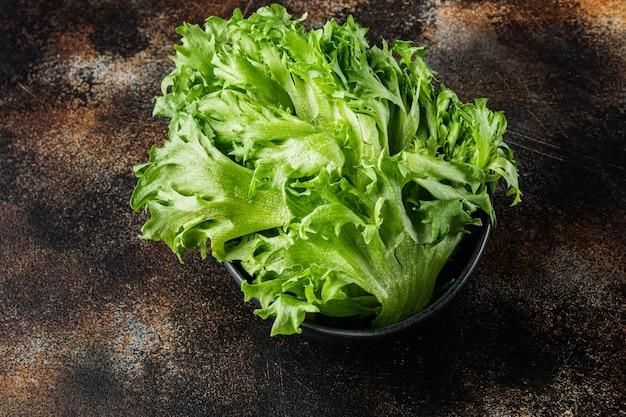 Świeże organiczne zielone liście sałaty batavia, na starym ciemnym rustykalnym tle