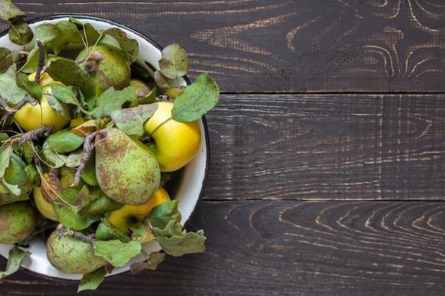 Świeże organiczne żółte jabłka i zielone gruszki w żelaznej misce na naturalnym brązowym tle drewnianych