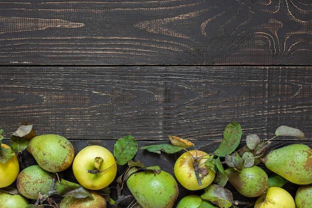 Świeże organiczne żółte jabłka i zielone gruszki z liśćmi na naturalnym brązowym tle drewnianych