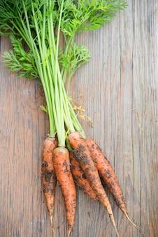 Świeże organicznie ogrodowe marchewki na drewnianym stole, odgórny widok