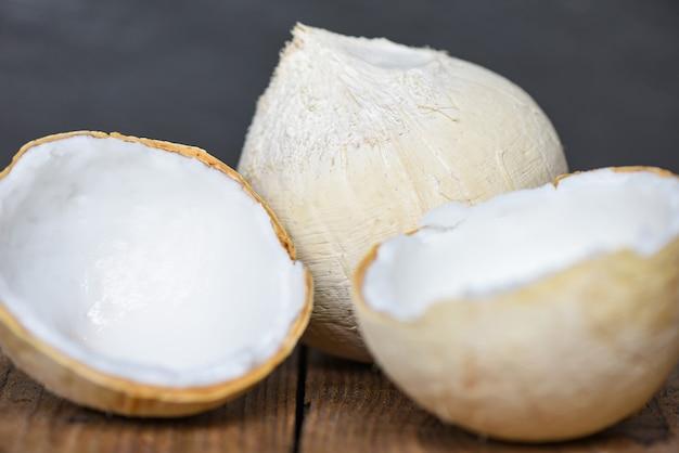 Świeże orzechy kokosowe i pokrój pół kokosa do jedzenia na drewnianym stole