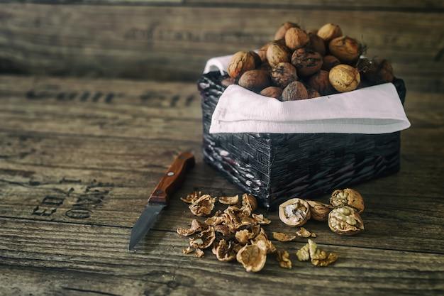 Świeże orzechy włoskie w koszu i nożu na tle jesieni na starym drewnianym stole,