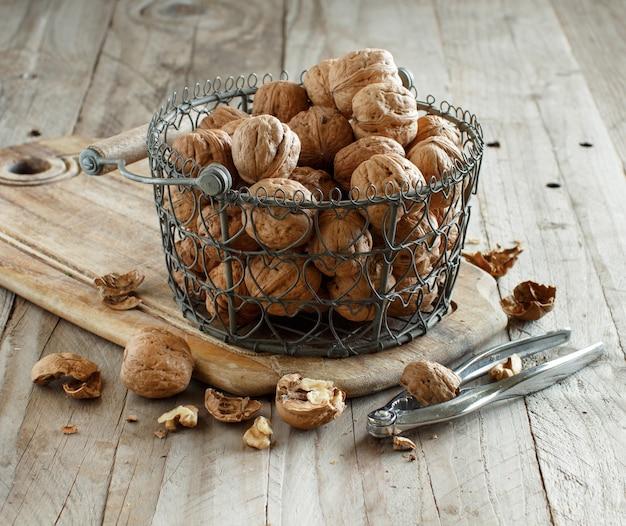 Świeże orzechy włoskie w koszu z dziadkiem do orzechów na starym drewnianym stole