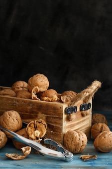Świeże orzechy włoskie z dziadkiem do orzechów na niebieskim drewnianym stole