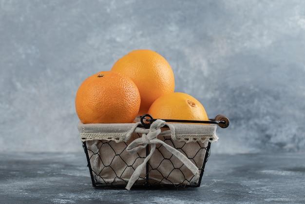 Świeże orzeźwiające pomarańcze w koszu na marmurowym stole.