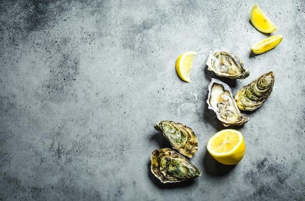Świeże ostrygi, ćwiartki cytryny. rustykalne tło kamień. otwarte świeże surowe ostrygi.