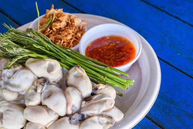 Świeże ostrygi na talerzu z sosem z warzyw i owoców morza, tajskie lokalne jedzenie.