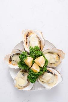 Świeże ostrygi w białym talerzu z lodem i cytryną na drewnianym biurku