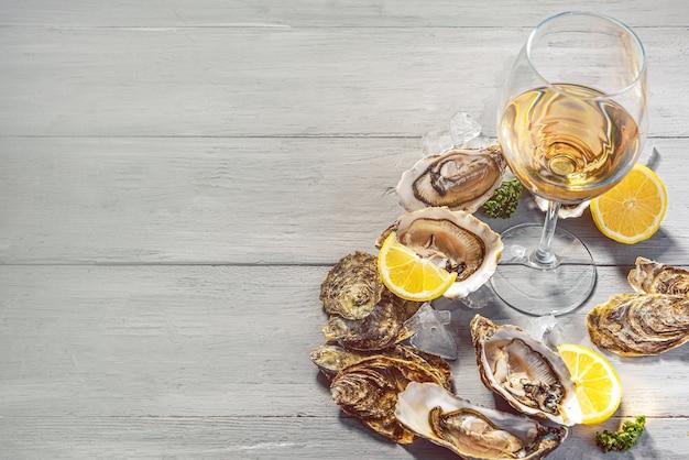Świeże ostrygi z cytryną, lodem i białym winem