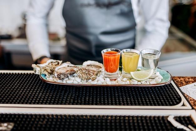 Świeże otwarte ostrygi z zestawem pędów koktajli alkoholowych podawane na stole. delikatesy z owoców morza?