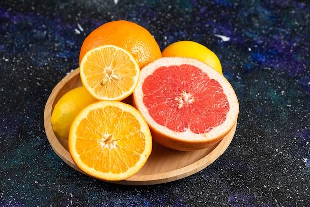Świeże owoce cytrusowe pół cięte na drewnianym talerzu.