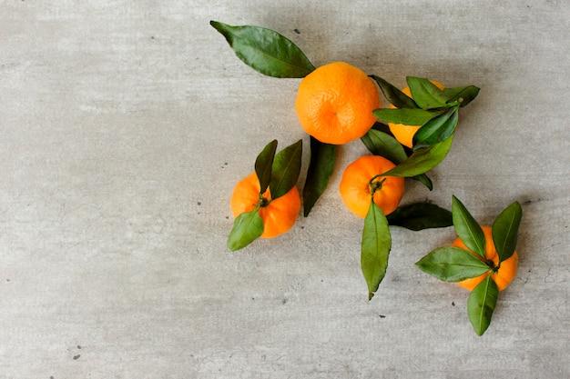 Świeże owoce cytrusowe z liśćmi: cytryny, pomarańcze, mandarynki w drewnianym pudełku