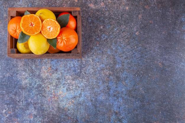 Świeże owoce cytrusowe z liśćmi umieszczone w starym drewnianym pudełku.