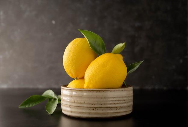 Świeże owoce cytryny na ciemnym, czarnym tle w misce