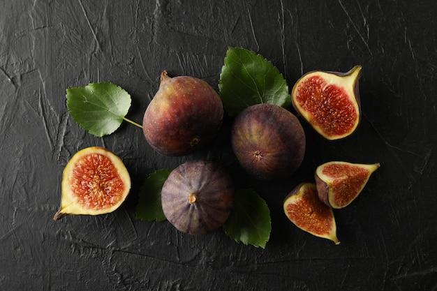 Świeże owoce figowe, plastry i liście na czarny, widok z góry