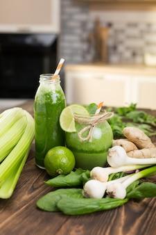 Świeże owoce i butelka z zielonymi koktajlami na kuchennym stole
