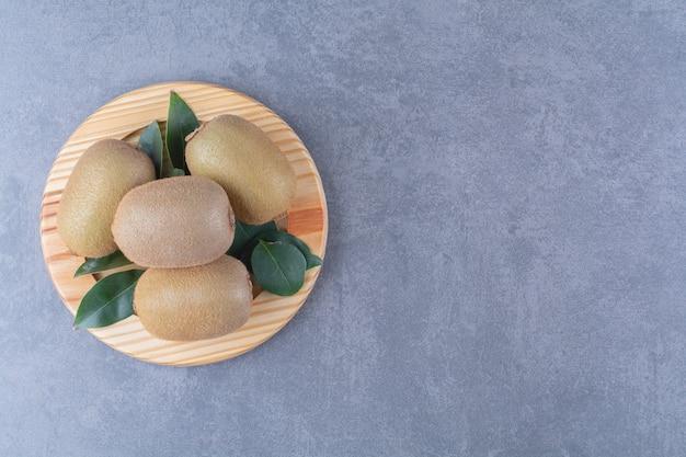 Świeże owoce kiwi na drewnianym talerzu na marmurowym stole.