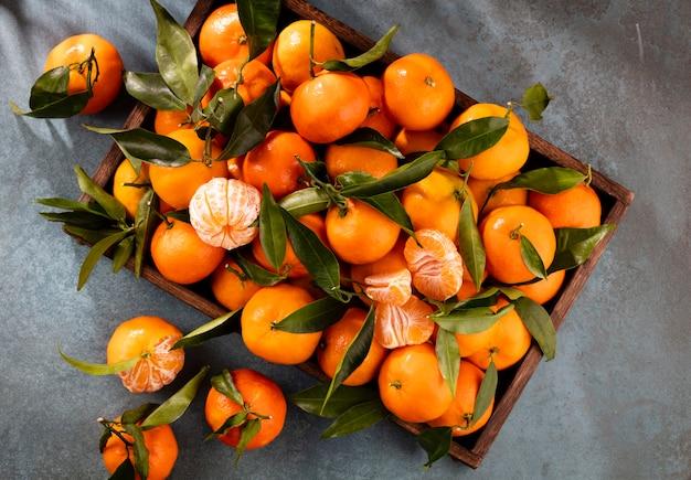 Świeże owoce mandarynki lub mandarynki z liśćmi w drewnianym pudełku, widok z góry