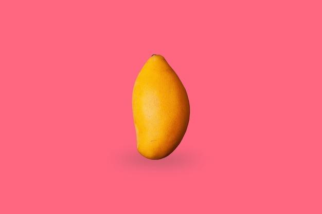 Świeże owoce mango na różowym tle.
