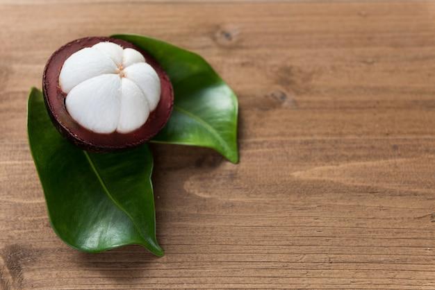 Świeże owoce mangostanu na drewnianym stole z zielonym liściem
