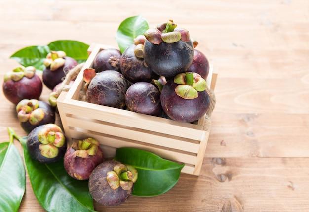 Świeże owoce mangostanu w koszu na drewnianym stole